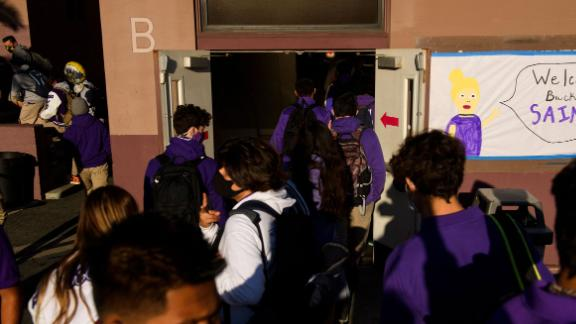 Students return to in-person learning at St. Anthony Catholic High School during the Covid-19 pandemic on March 24, 2021 in Long Beach, California. - The school of 445 students implemented a hybrid learning model, with approximately 60 percent of students returning to in an in-person classroom learning environment with Covid-19 safety measures including face masks, social distancing, plexiglass barriers around desks, outdoor spaces, and schedule changes. (Photo by Patrick T. FALLON / AFP) (Photo by PATRICK T. FALLON/AFP via Getty Images)