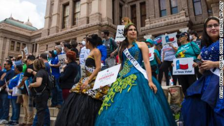 Activists with Jolt Action dressed in quinceañera attire in front of the Capitol.