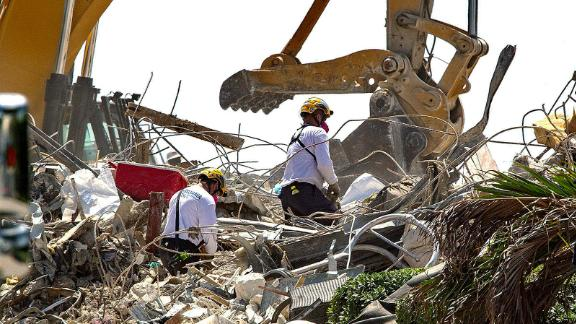 Rescue teams from Pennsylvania, search the rubble of the Champlain Towers South Thursday July 8, 2021 in Surfside, Fla. Rescue workers now focused on finding remains instead of survivors in the rubble of a Florida condominium collapse paused briefly atop the pile Thursday to mark the two-week anniversary of the disaster but said they had no plans to pull back during the recovery effort.  (Pedro Portal/Miami Herald via AP)