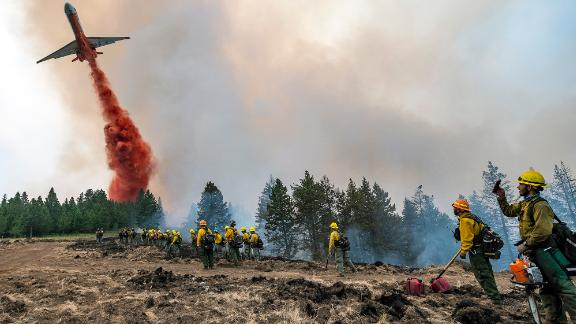 Wildland firefighters watch and take video with their cellphones as a plane drops fire retardant on Harlow Ridge above the Lick Creek Fire, southwest of Asotin, Wash., Monday, July 12, 2021. The fire, which started last Wednesday, has now burned over 50,000 acres of land between Asotin County and Garfield County in southeast Washington state. (Pete Caster/Lewiston Tribune via AP)