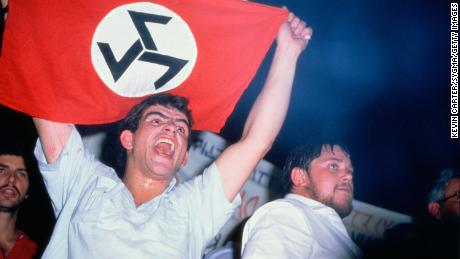 White South African man holds up a flag for the Afrikaner Resistance Movement (AWB), one of many groups that once threatened to push the nation into a civil war.