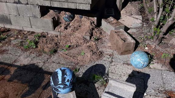 He removed a cinder block from the porch and saw a blue & black sphere.