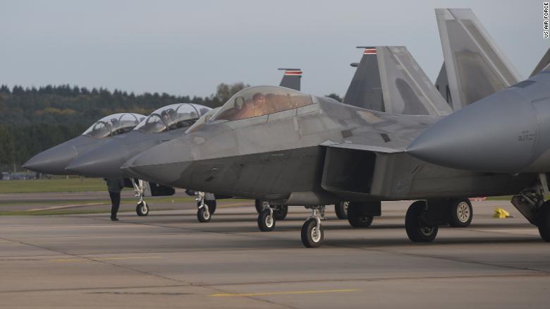 تصطف طائرة F-22 Raptor التابعة للقوات الجوية الأمريكية بجوار ثلاث طائرات F-15E Strike Eagles في سلاح الجو الملكي Lakenheath ، إنجلترا ، في عام 2017.
