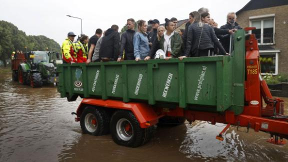 People ride on a trailer as the Dutch fire brigade evacuate people from their homes in South Limburg.