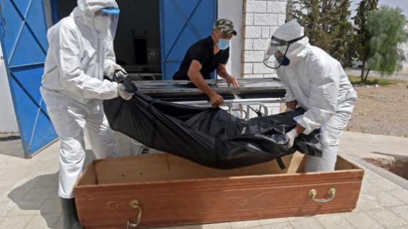 The body of a Covid-19 victim is placed into a casket at the Ibn al-Jazzar hospital in the Tunisian city of Kairouan on July 4, 2021.