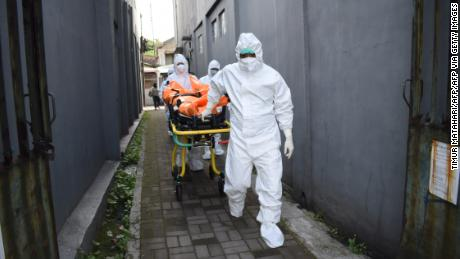 Health workers remove the body of a deceased Covid-19 victim on Wednesday while in self-isolation at home in Indonesia.