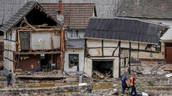 Men walk by damaged homes in Schuld, Germany.