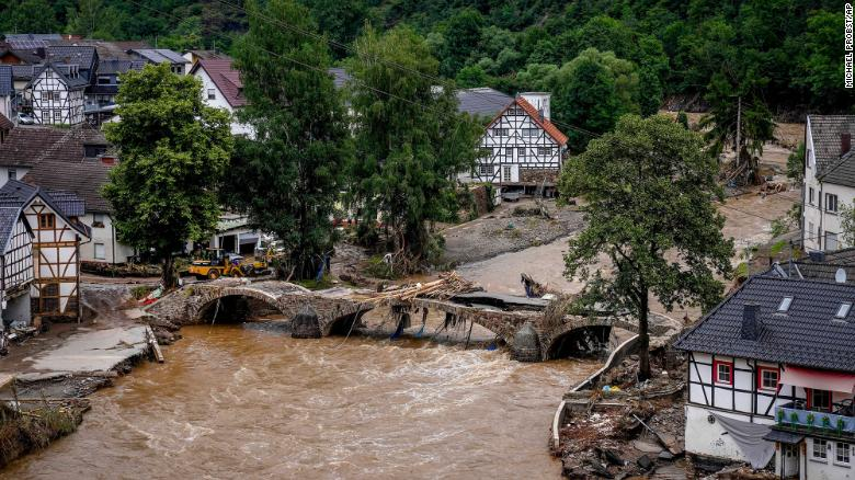 Water from the Ahr River flows past a damaged bridge in Schuld.