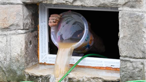A resident uses a bucket to remove water from a house cellar in Hagen, Germany.