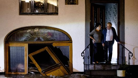 A man and woman stand on the stoop of their home as they look at floodwaters in Geulle, Netherlands.