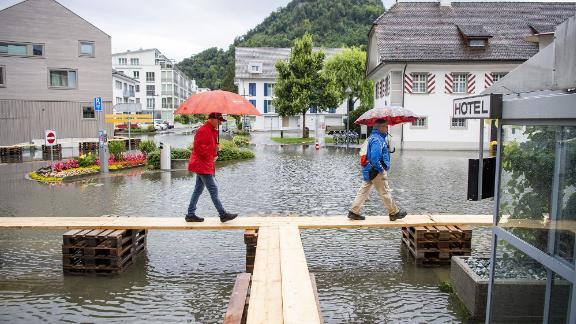 People walk over floodwaters in Stansstad, Switzerland.