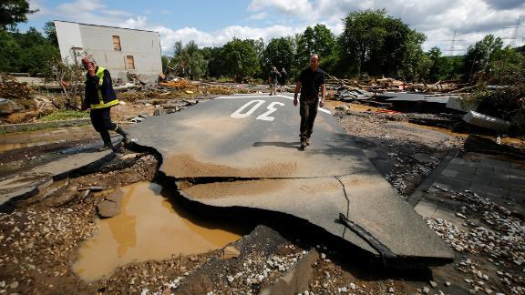 People walk on a damaged road in Bad Neuenahr-Ahrweiler, Germany.