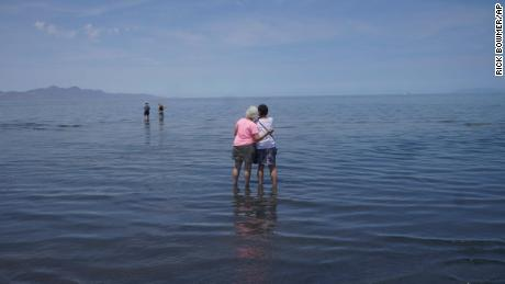 Visitors stand in June in the shallow waters of the Great Salt Lake.