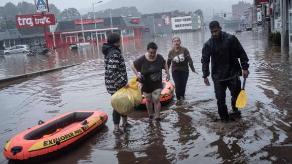 People use rafts to evacuate after the Meuse River broke its banks during heavy flooding in Liege, Belgium.