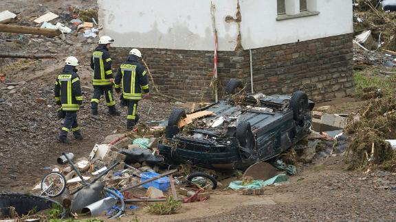 Firefighters walk past a car that was damaged by flooding in Schuld, Germany.