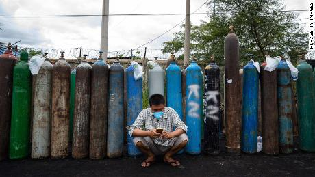 A man uses his mobile phone in front of empty oxygen canisters, which people are waiting to fill up, outside a factory in Mandalay, on July 13.