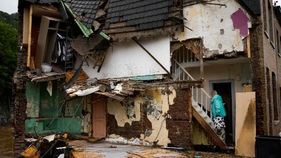 A woman walks up the stairs of her damaged house in Ensival, Belgium.