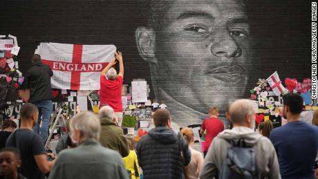 Les gens regardent les messages de soutien et la peinture murale récemment réparée de Rashford, qui est affichée sur le mur d'un café sur Copson Street, Withington, après avoir été défigurée par des vandales.