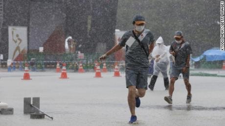 Staff members run to escape a rainstorm during an Olympic flame-lighting ceremony in Mizuho, western Tokyo, on July 11, 2021.