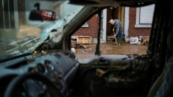 A man brushes water and mud out of his flooded house in Ensival, Belgium, on July 16.