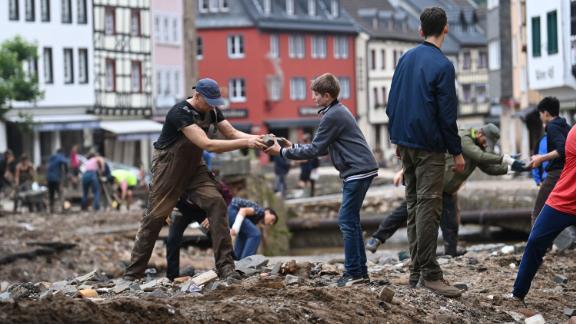 People collect debris in the pedestrian area of Bad Muenstereifel, western Germany.