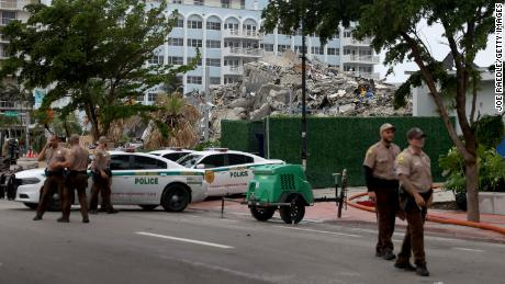 Miami-Dade police assist at the search and rescue booth near the completely collapsed 12-story Champlain South Towers on July 6, 2021 in Surfside, Florida.