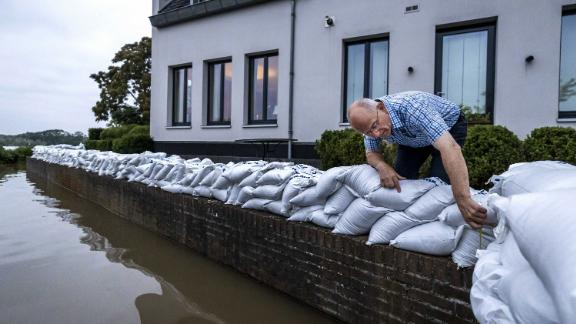 An Arcen resident looks at the rising water of the river Maas.