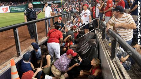 Fans take cover after apparent gun shots were heard during the game between the Washington Nationals and the San Diego Padres at Nationals Park.
