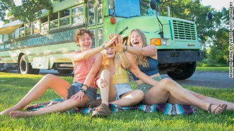 From left to right, Bekah King, Morgan Tabor, and Abi Roberts in front of the BAM bus.