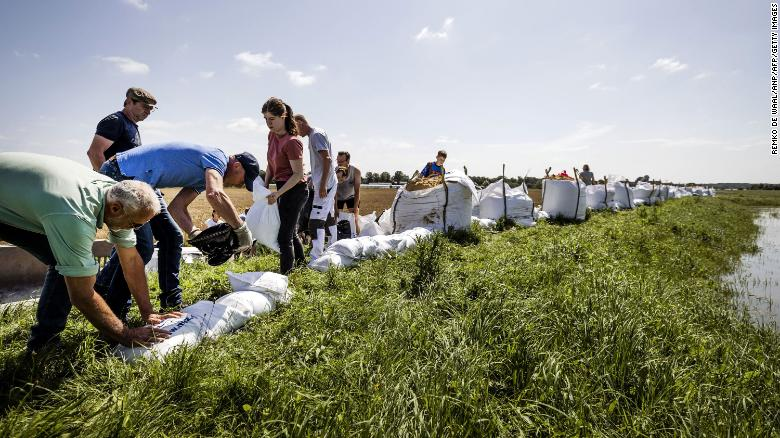 People build flood defenses using sandbags following heavy rains and floods in the Limburg province of the Netherlands.