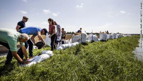 As pessoas constroem defesas contra inundações com sacos de areia após fortes chuvas e inundações em Limburg, na Holanda.