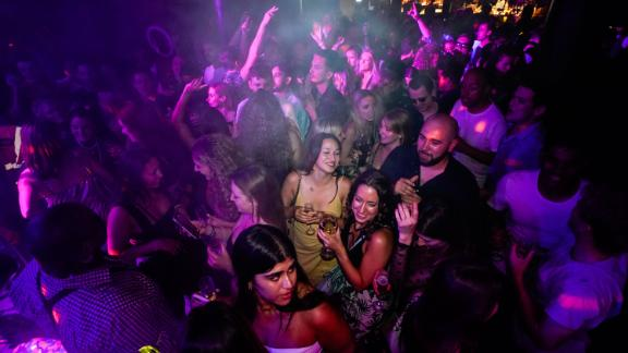 People hit the dance floor at The Piano Works in London early Monday.