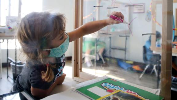 A student writes on a divider which is used for learning in a socially distanced protective desk at Westwood STAR Tutoring & Enrichment Center on September 2, 2020 in Los Angeles, California.