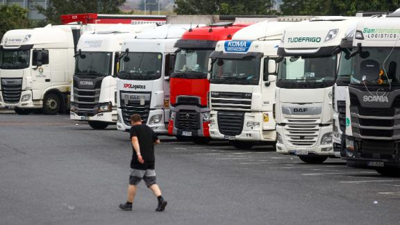 """A driver passes a row of heavy goods vehicles (HGV) at a service station near Chafford Hundred, U.K., on Tuesday, July 13, 2021. Almost a third of U.K. logistics companies expect to face trucker shortages this year, and a 10th say recruitment issues will pose an """"extreme barrier"""" to the recovery of their business from the pandemic. Photographer: Chris Ratcliffe/Bloomberg via Getty Images"""