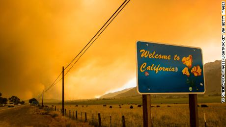 MARKLEEVILLE, CALIFORNIA, UNITED STATES - 2021/07/17: A sign welcoming people to California seen in front of the Tamarack fire. The Tamarack fire continues to burn through more than 21,000 acres and is currently 0% contained. It was started by a lightning strike. (Photo by Ty O'Neil/SOPA Images/LightRocket via Getty Images)