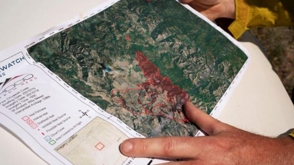 A member of the Northwest Incident Management Team 12 holds a map of the Chuweah Creek Fire as wildfires devastated Nespelem, Washington, on Friday, July 16.
