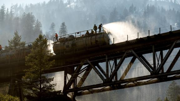 Firefighters spray water from the Union Pacific Railroad's fire train while battling the Dixie Fire in California's Plumas National Forest on July 16.