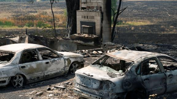 Burned cars sit outside a home that was destroyed by the Chuweah Creek Fire in Nespelem, Washington.