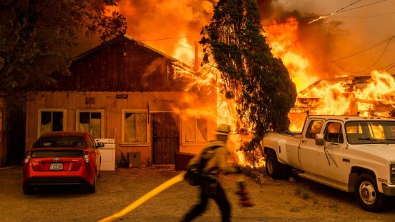 """Fire consumes a home as the Sugar Fire, part of the Beckwourth Complex Fire, tears through Doyle, California, on July 10. It's the <a href=""""https://www.cnn.com/2021/07/14/weather/california-doyle-second-wildfire-in-a-year/index.html"""" target=""""_blank"""">second time in less than a year</a> that the small town has been ravaged by a wildfire."""