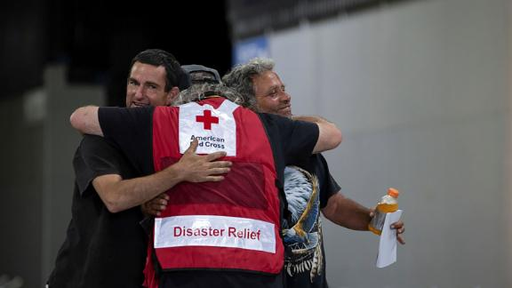 Men hug a member of the Red Cross at a Bootleg Fire evacuation center in Klamath Falls, Oregon, on July 12.