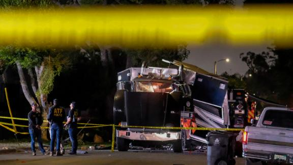 ATF investigators are seen next to the remains of an armored LAPD vehicle after fireworks exploded.