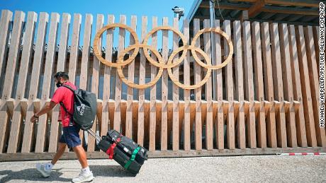 أحد أعضاء الوفد المكسيكي يمر بالحلقات الأولمبية عند مدخل القرية الأولمبية.