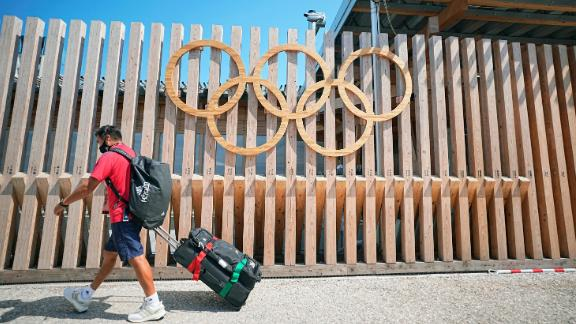 19 July 2021, Japan, Tokio: A man from Team Mexico walks past Olympic rings at the entrance to Olympic Village. The Olympic Village is a housing development that will house the participants of the 2020 Olympic Games. The 2020 Tokyo Olympics will be held from July 23, 2021 to Aug. 8, 2021. Photo by: Michael Kappeler/picture-alliance/dpa/AP Images