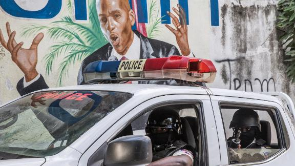 A police convoy drives past a wall painted with the president's image down the alley of the entrance to the residence of the president in Port-au-Prince on July 15, 2021, in the wake of Haitian President Jovenel Moise's assassination on July 7, 2021. - The assassination of Jovenel Moise by armed mercenaries was planned in the neighboring Dominican Republic, say Haitian police, who announced the detention of the slain president's chief bodyguard and three other members of his security detail. (Photo by Valerie Baeriswyl / AFP) (Photo by VALERIE BAERISWYL/AFP via Getty Images)