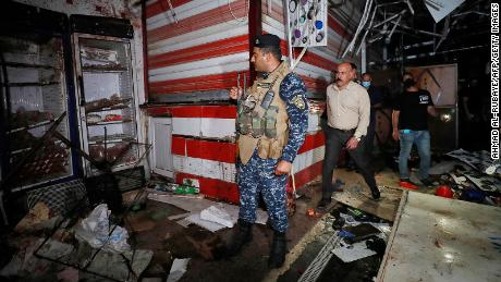 イラク人が7月19日、バグダッド東部の市場で爆発現場を調査している。