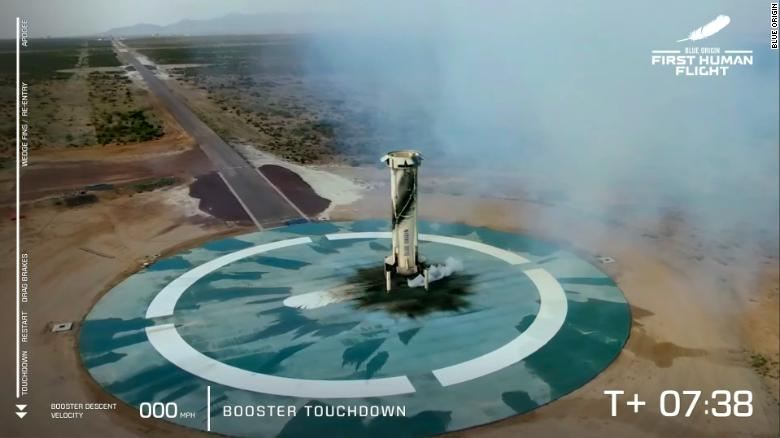 The New Shepard rocket booster rests on the ground after launching the capsule into space.