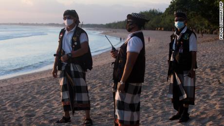 Penjaga keamanan tradisional dari pulau Bali berpatroli di Pantai Kuta sambil memberlakukan pembatasan darurat untuk membantu mengekang penyebaran virus corona pada 6 Juli 2021.