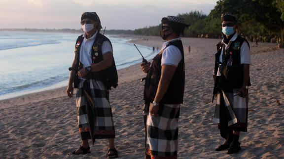 Balinese traditional security guards patrol at Kuta beach during the imposition of an emergency restriction to help curb the spread of coronavirus on July 6, 2021.