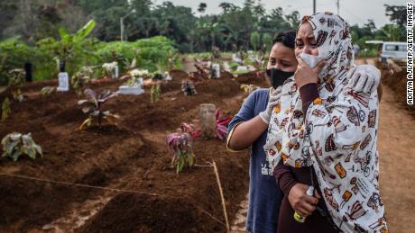 Seorang ibu berkabung dengan putranya saat pemakaman ibunya di pemakaman Mulyaharja untuk korban virus corona Covid-19, di Bogor, Jawa Barat, pada 8 Juli 2021.