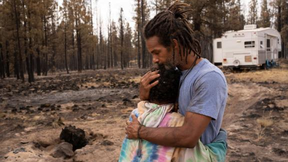 Nicolas Bey, 11, hugs his father, Sayyid, near a donated trailer they are using after their home was burned in the Bootleg Fire near Beatty, Oregon.